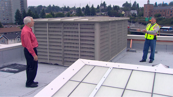 Paul Wight, a project manager on the John Marshall renovation, shows KING 5's Chris Ingalls the air intake on the school's roof.
