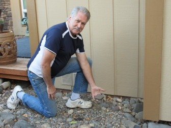 Ashland homeowner Doug Kay shows how he replaced shrubs near his home with rock as one way to help protect it from wildfire.