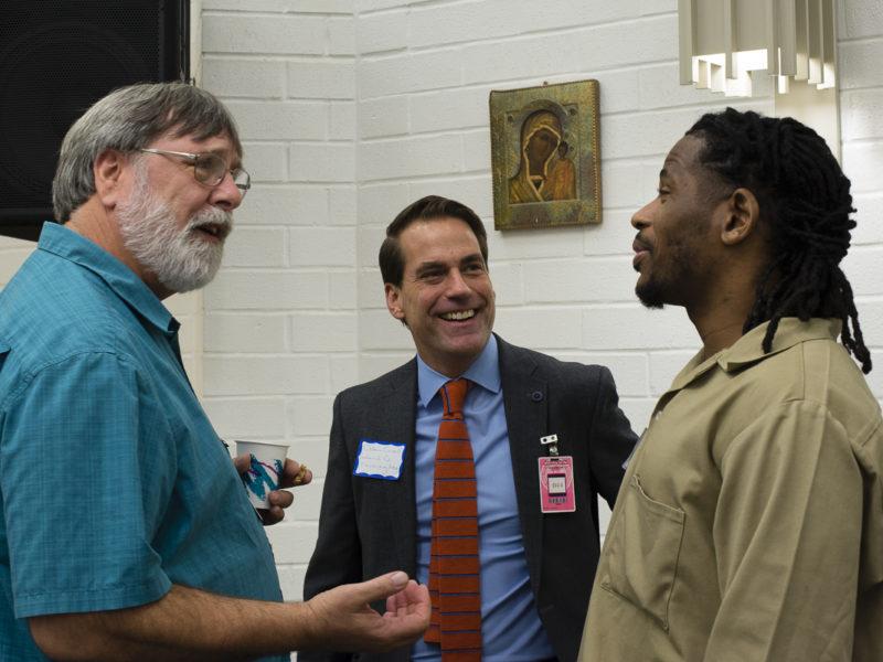 3 smiling men talking