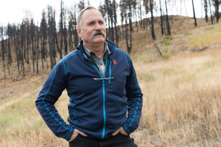 Portrait of former wildland firefighter Paul Hessburg standing in front of charred trees