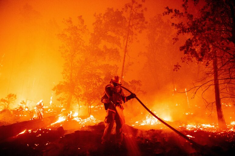 One firefighter confronts burning landscape with hose