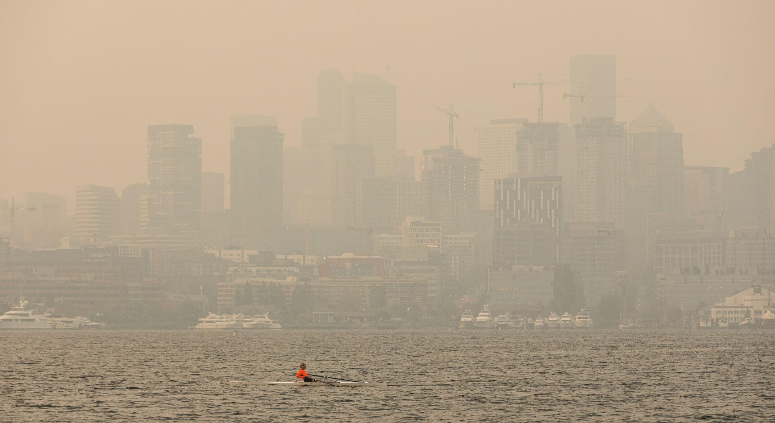 The Seattle skyline, heavily obscured by gray-orange smoke to the point where the buildings are barely visible. At the bottom, Lake Union, where a lone kayaker travels across in a bright orange shirt.