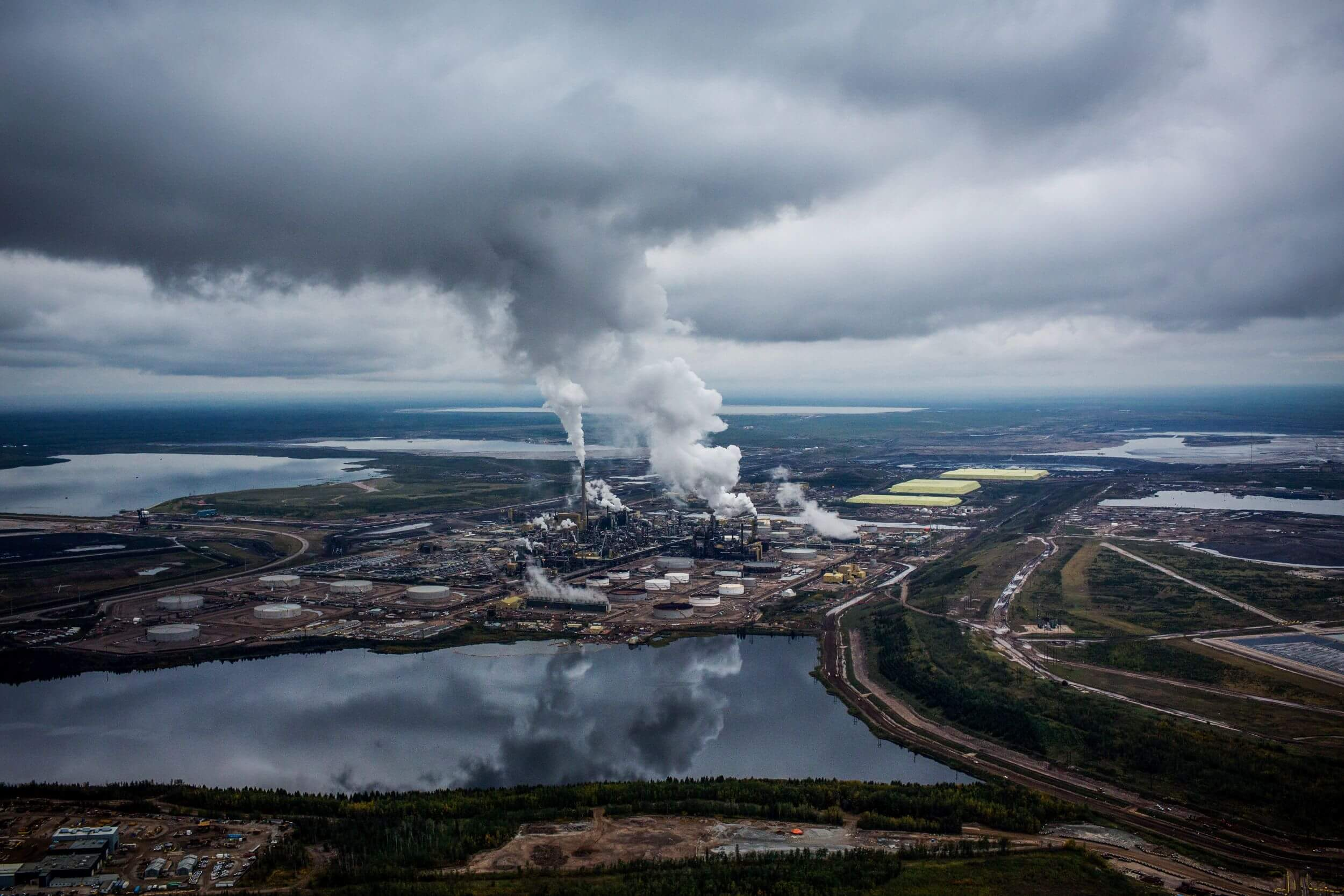 An aerial shot of a landscape of land and water, with cloudy skies above. In the center, an industrial plant, smoke rising.