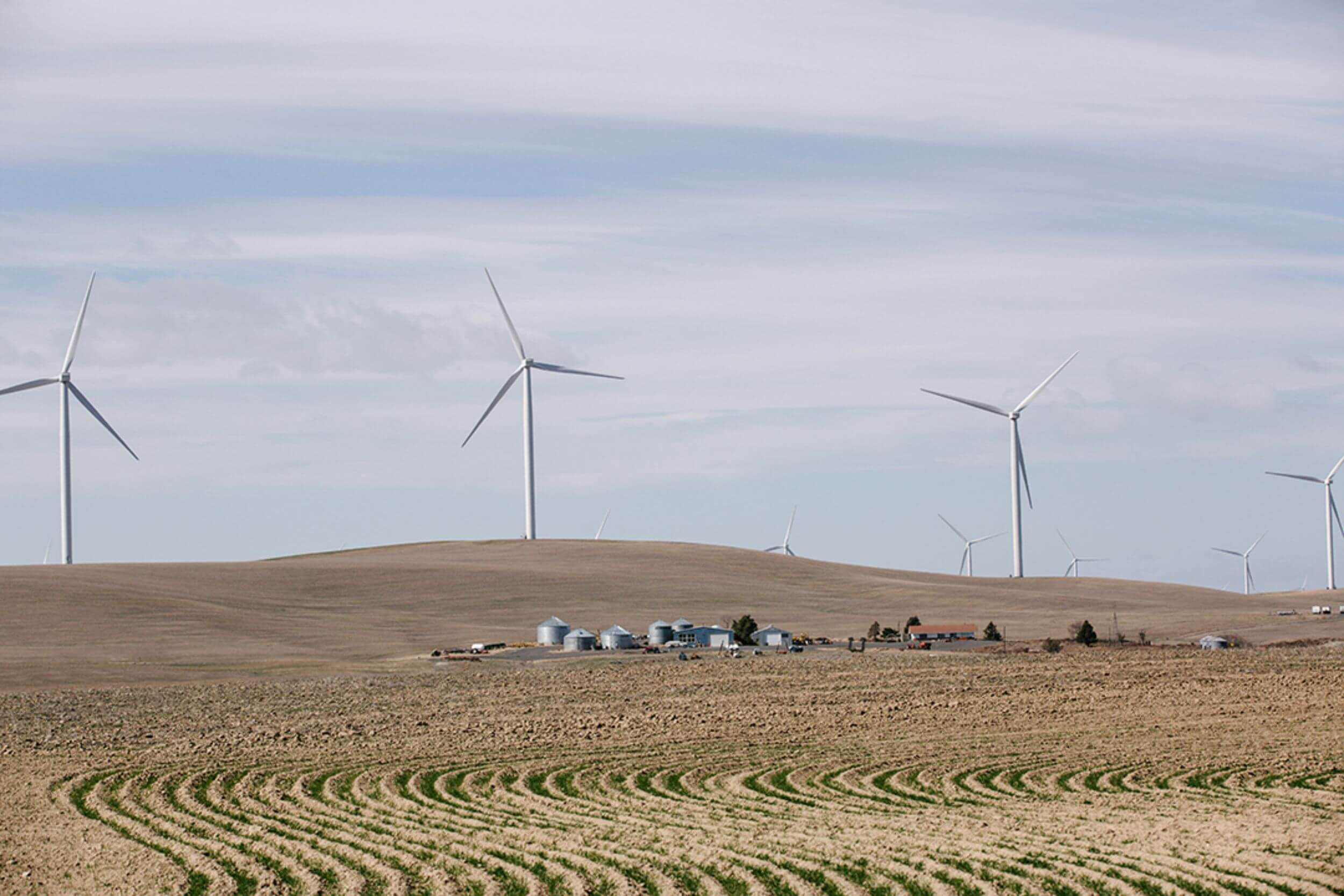A faraway shot of windmills on a brown hillside.