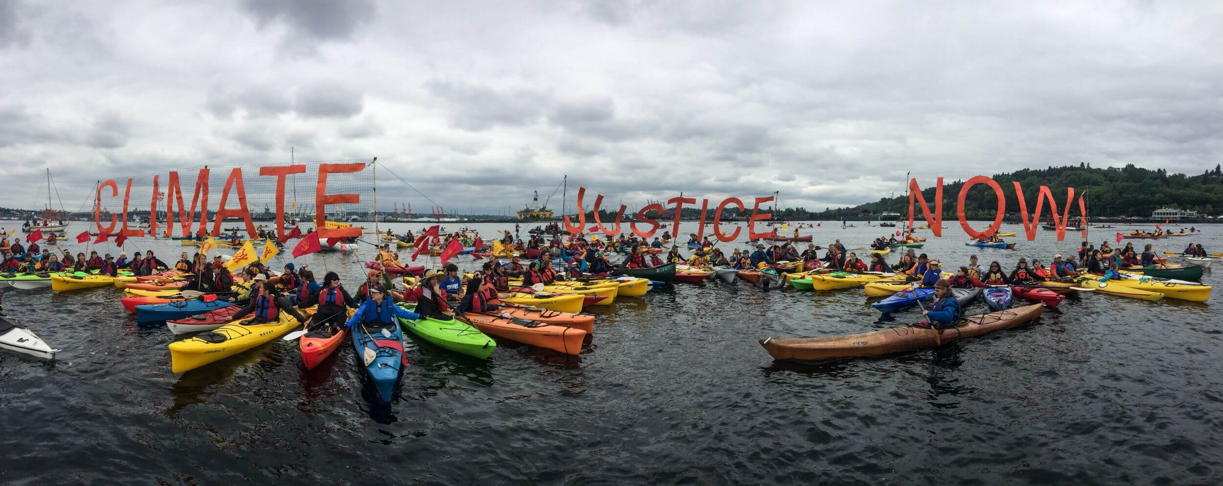 """Many kayakers on a body of water. Behind them, a giant sign reads """"CLIMATE JUSTICE."""" One lead kayaker is in front of them."""