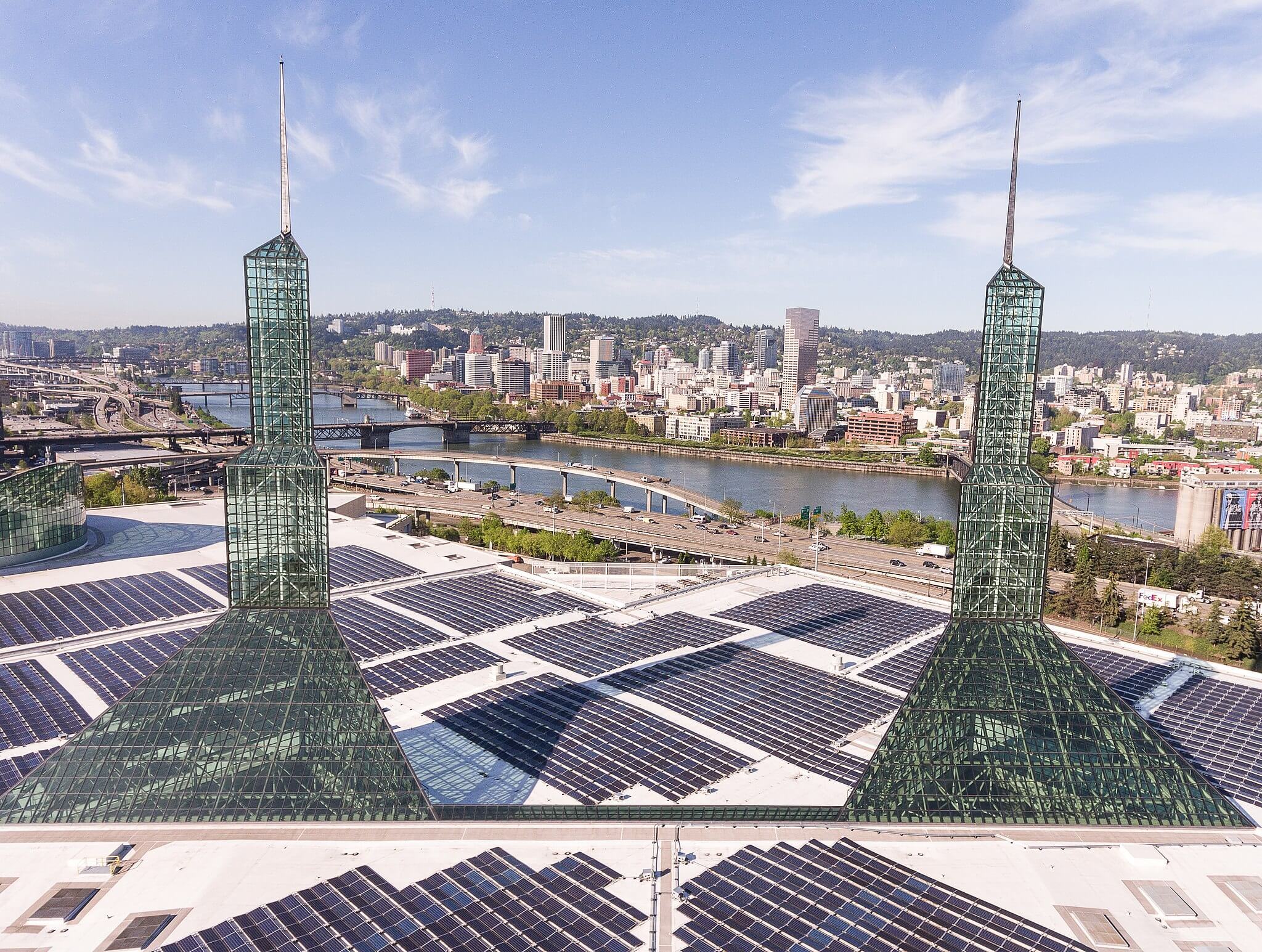An aerial shot of solar panels. In the background, a city skyline.