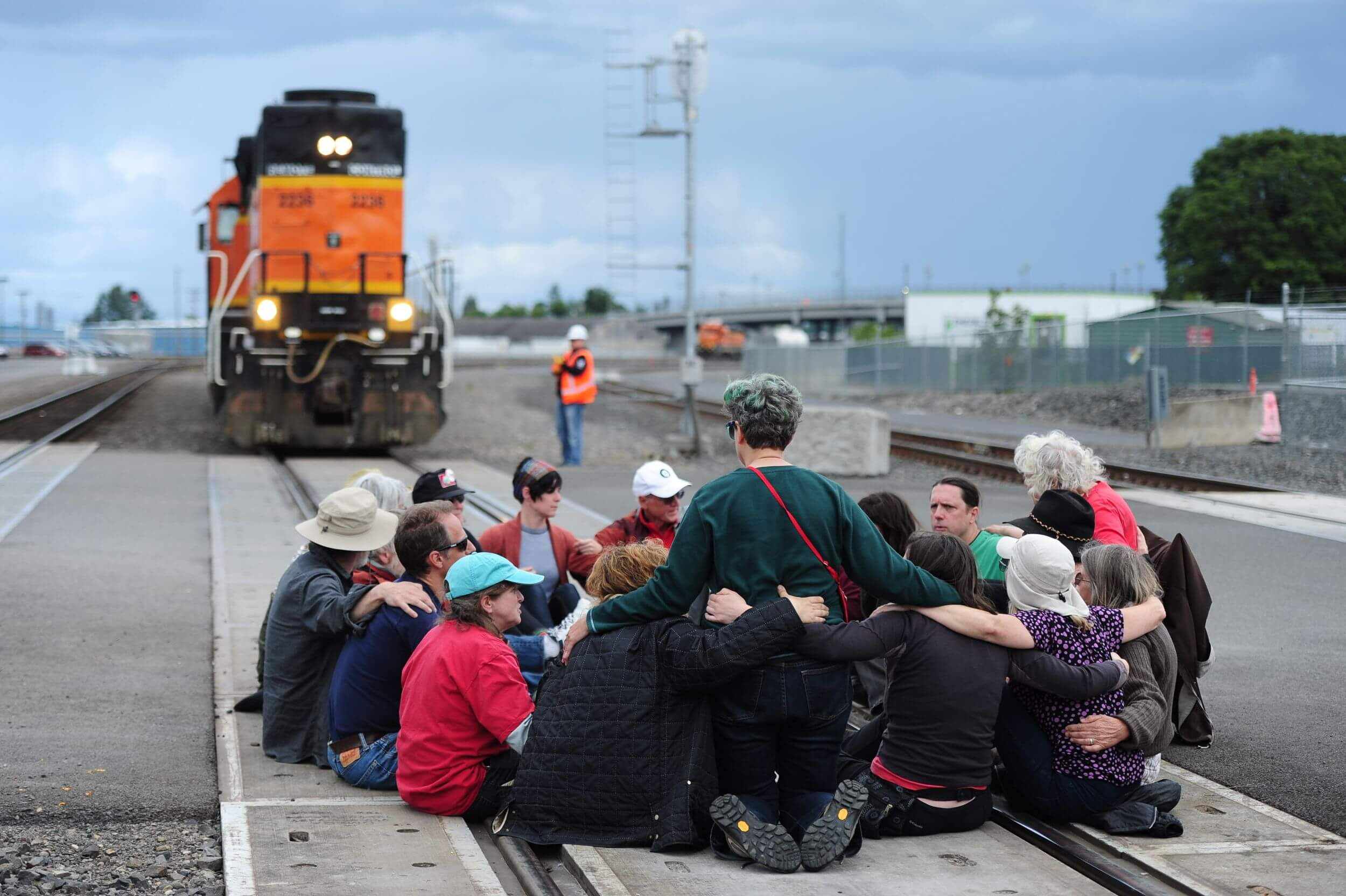A group of about 16 people sit cross-legged in a circle on a train track, blocking a train from moving past them.