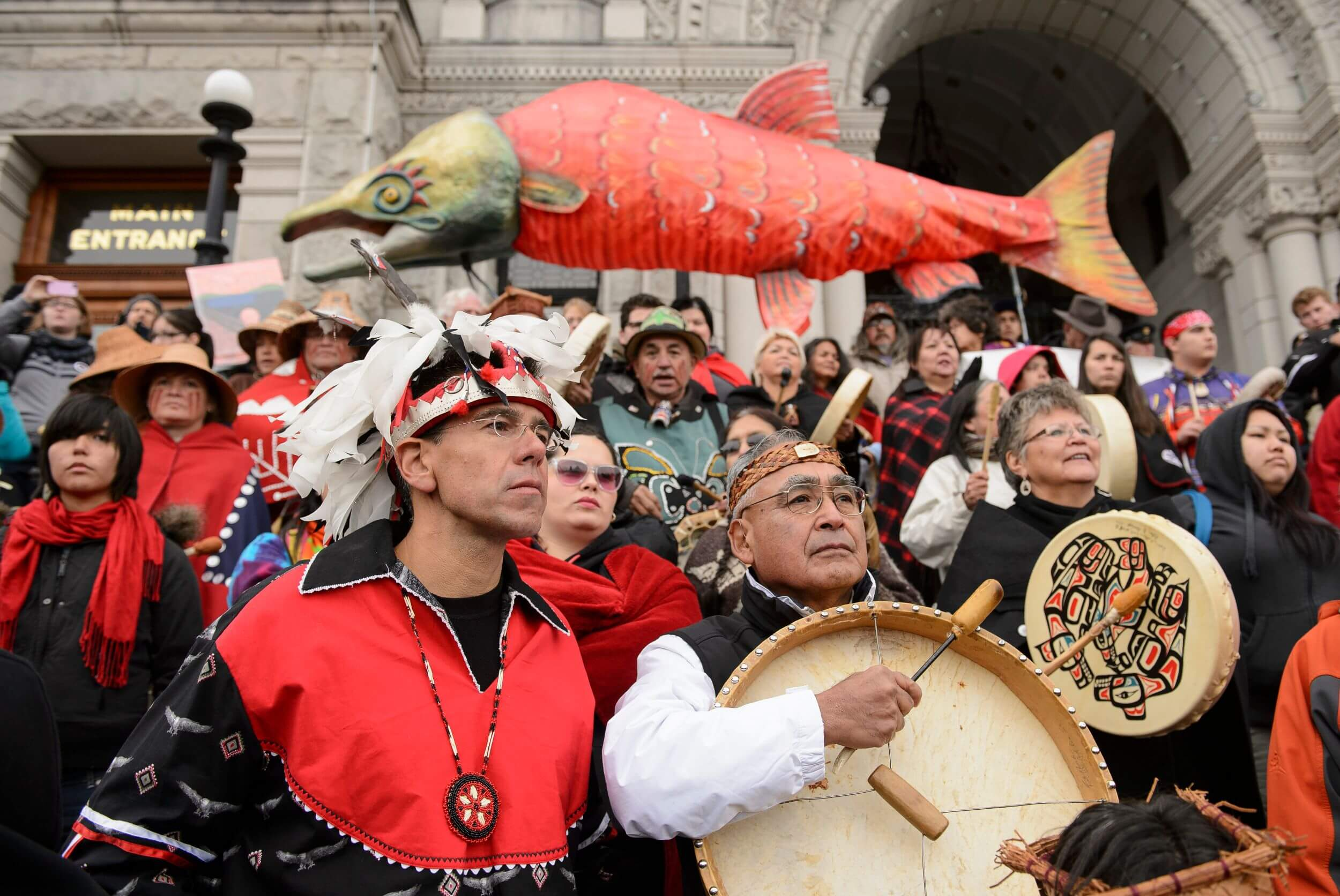 A close-up shot of people on the steps of a large building. Many are dressed in traditional indigenous clothing and hold drums. Above them, a large paper salmon.