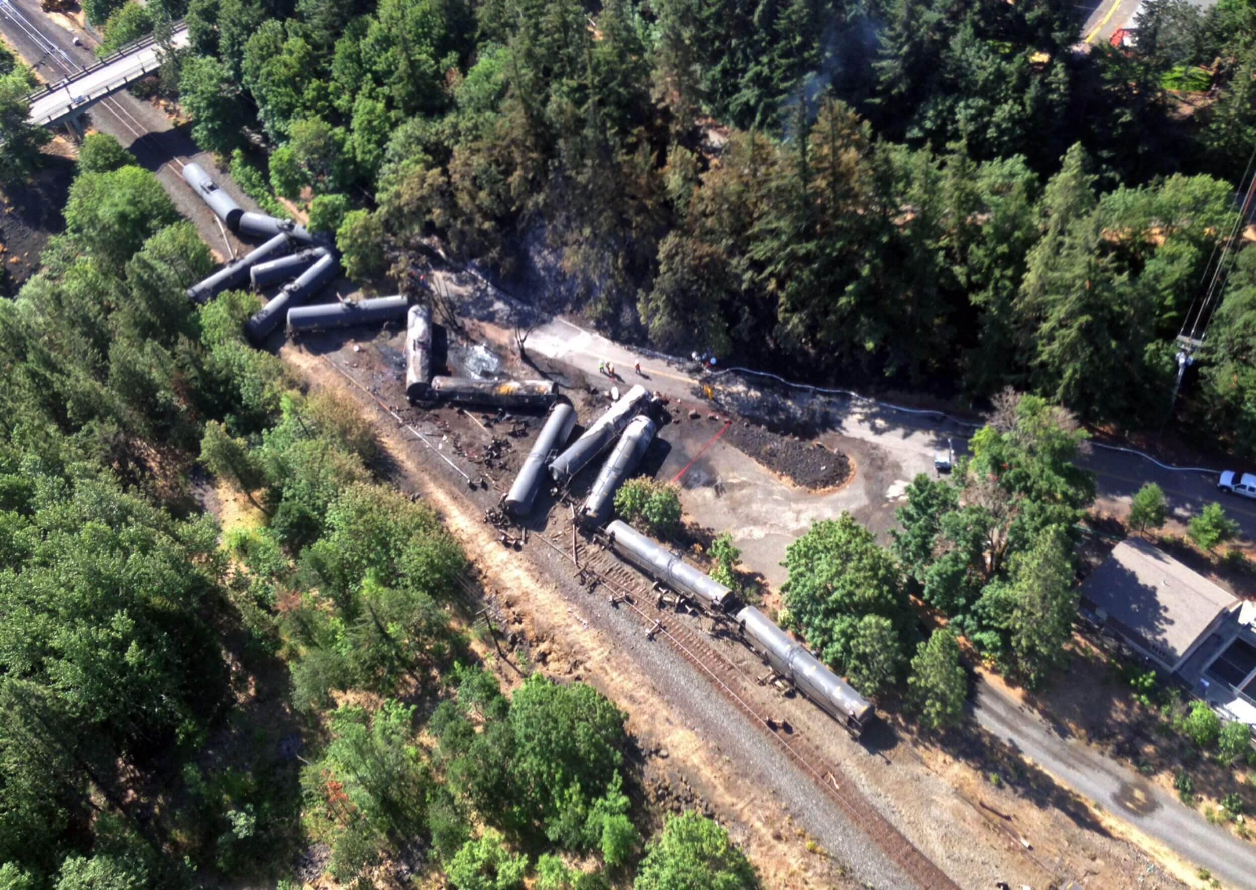 An aerial shot of a train that crashed on a track. It is surrounded by green trees.