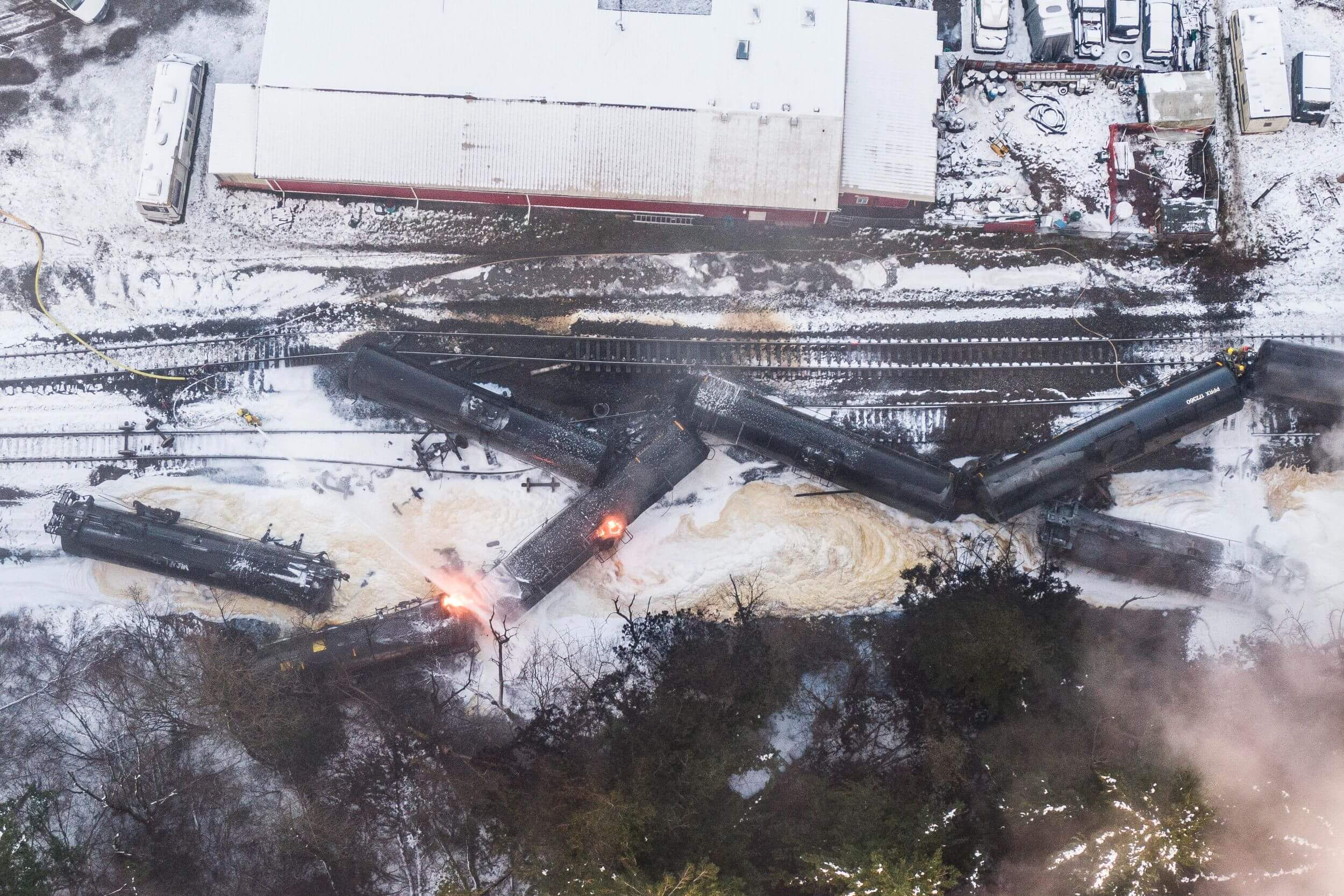 An aerial shot of a crashed train on tracks, surrounded by snow. Two parts of the train are lit up with fire.