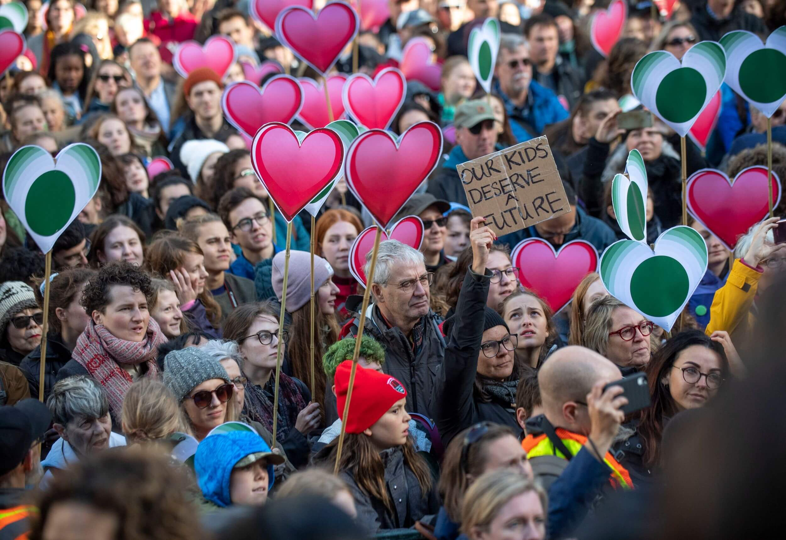 """The faces of a crowd of protestors. All are looking at something off-camera. Many hold paper pink hearts on sticks. One holds a cardboard sign that reads """"Our kids deserve a future."""""""