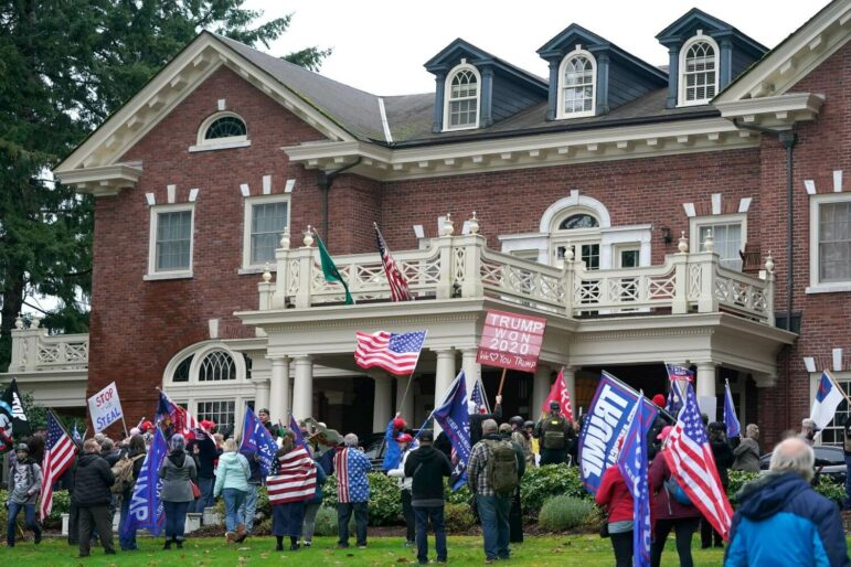 People with pro-Trump signs and American flags stand on the lawn of a large brick mansion.