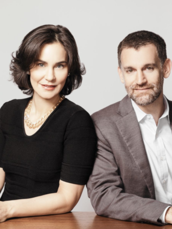 A professional headshot of two people sitting side-by-side against a white backdrop, dressed in business-professional clothing.