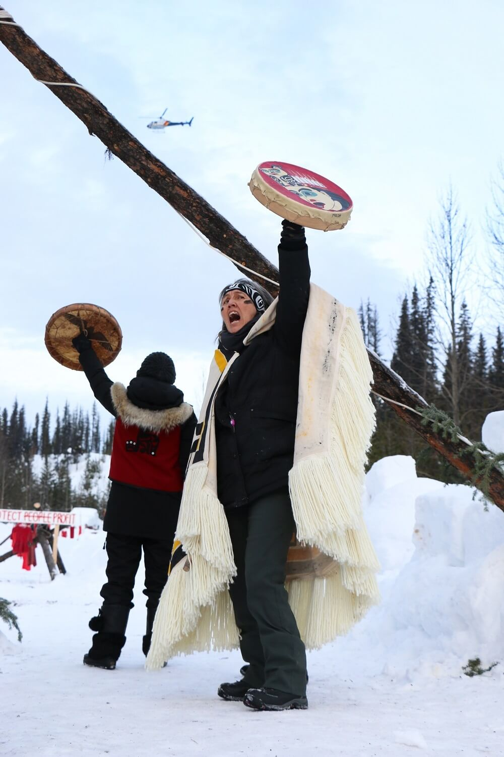 Two people in Indigenous clothing stage a protest.