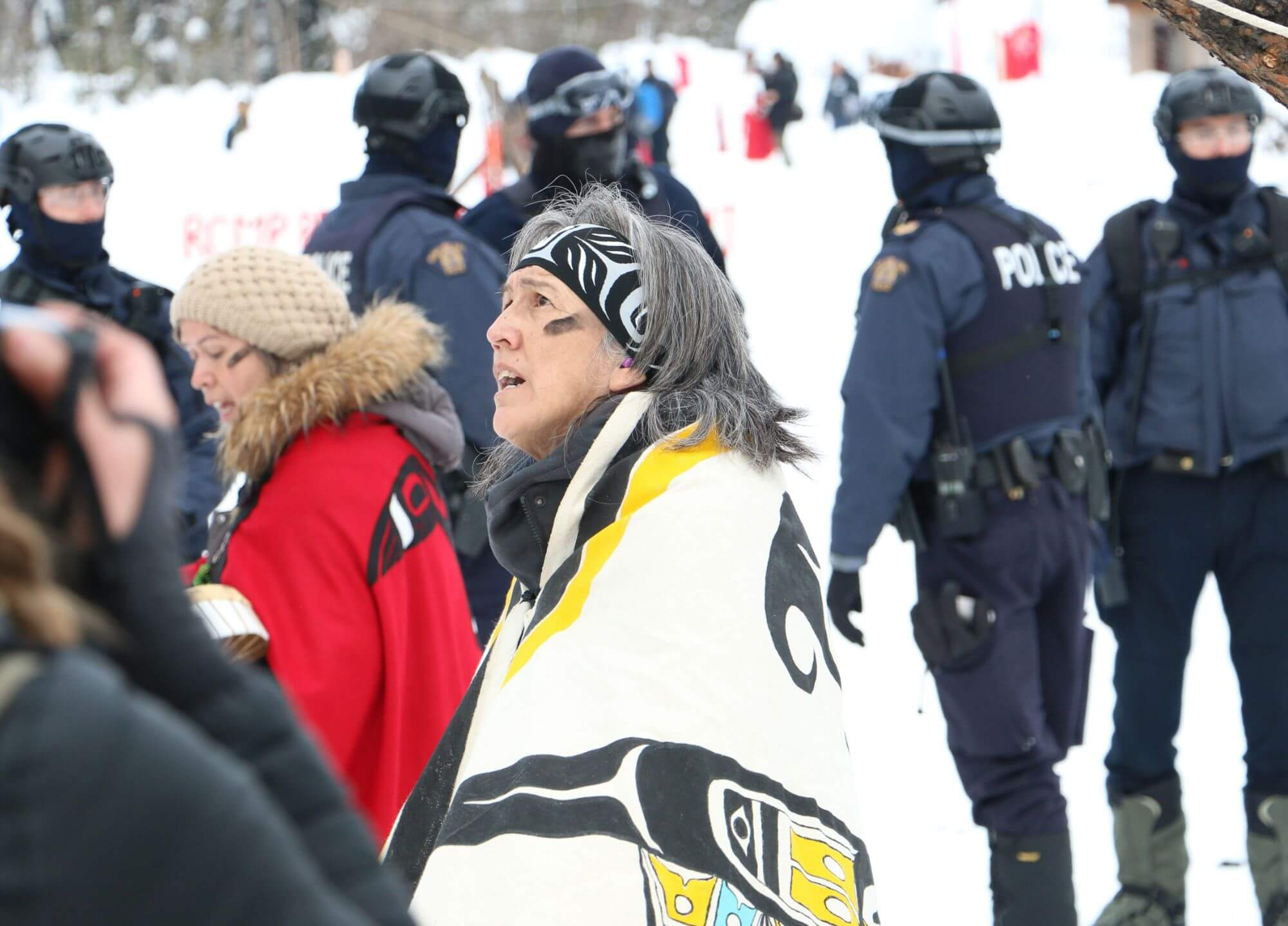 An Indigenous activist standing amid five police officers and two others.