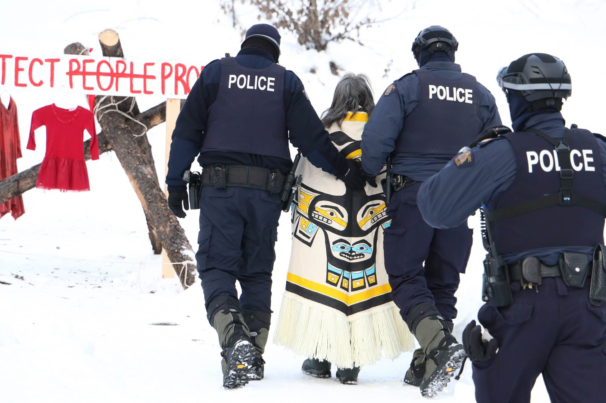 Three police officers escort a person in Indigenous clothing.