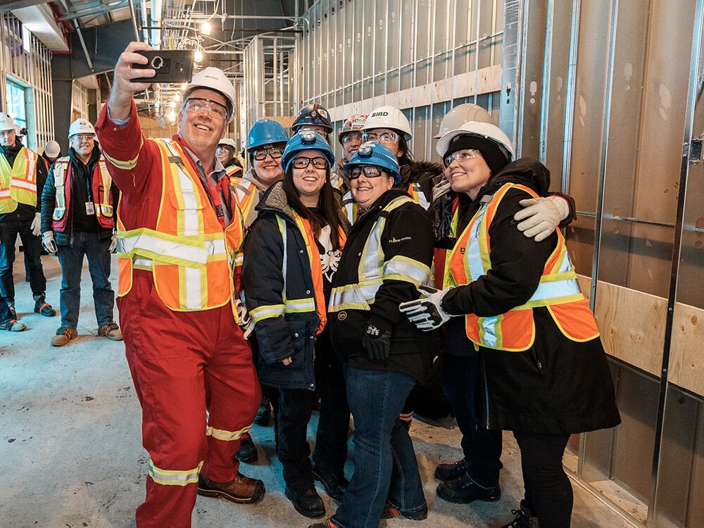 A group of people in neon construction vests and hard hats pose for a selfie.