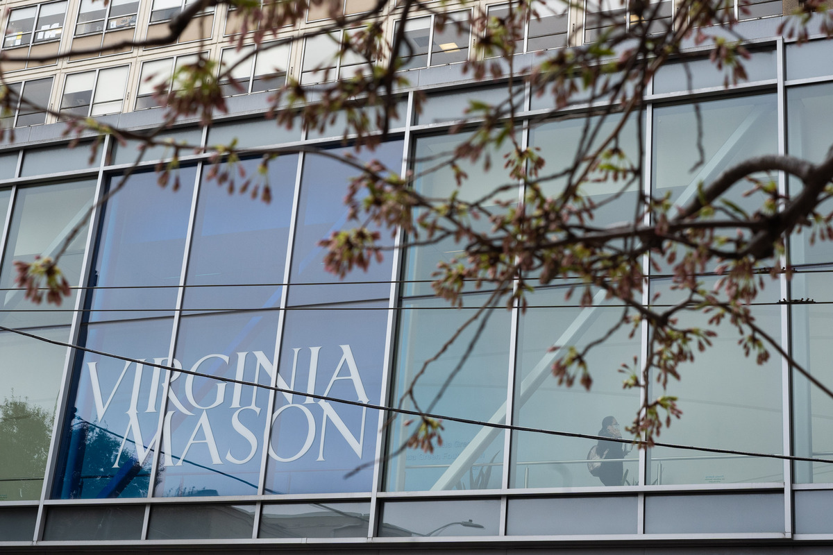 """The glass windows of a building, with the logo """"Virginia Mason"""" visible."""