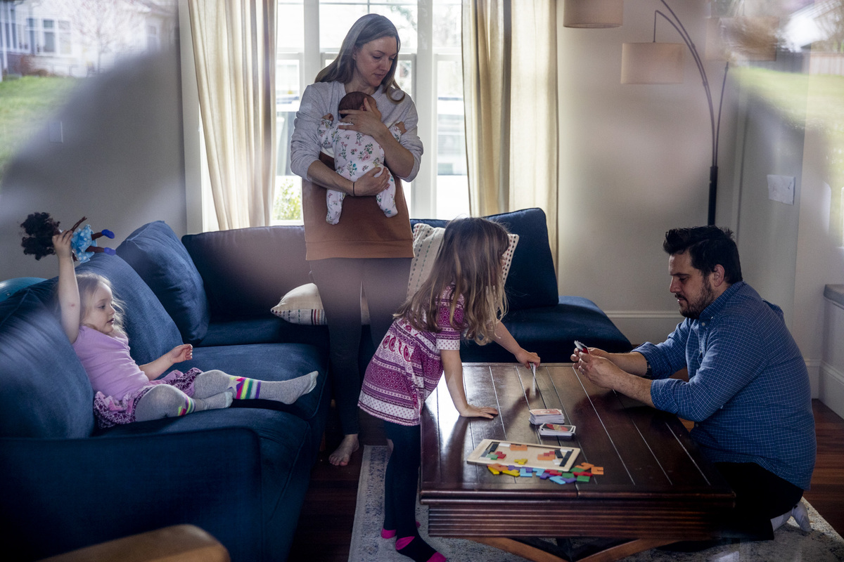 A family of two parents and three children sitting and playing together in a living room.