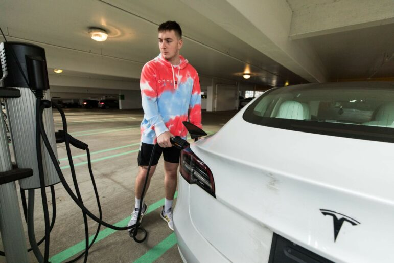 A person plugs their Tesla car into an electric charge.