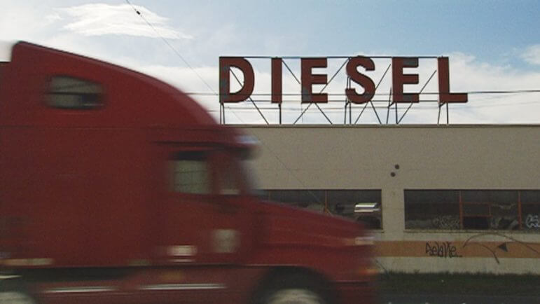 A red truck in front of a diesel sign.