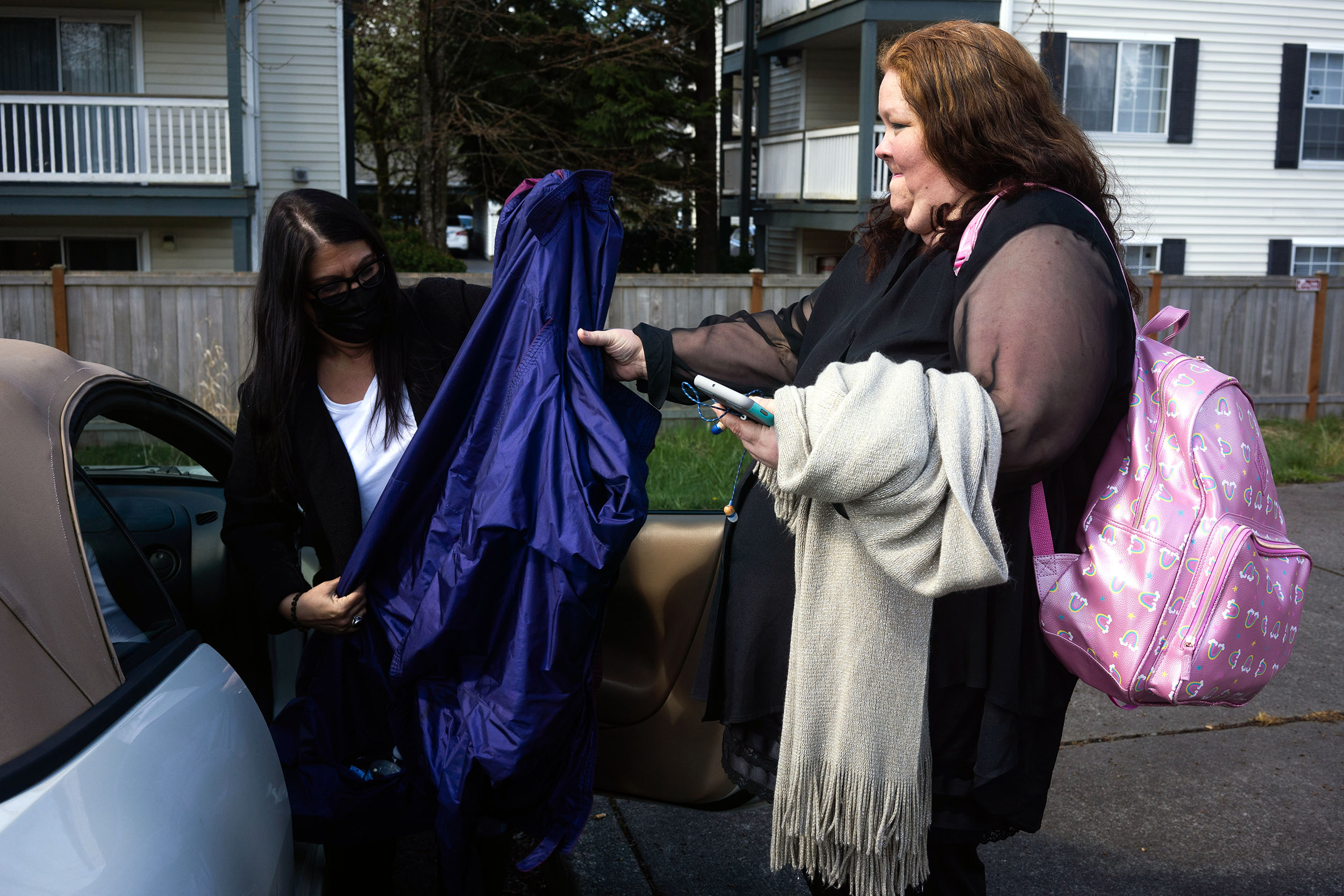 A woman grabs some clothing from another person who is unloading a car.