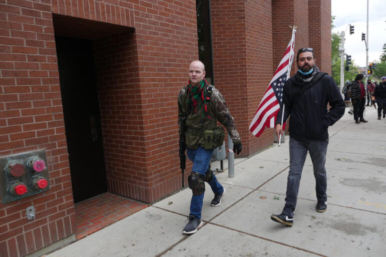 Two men, one armed with guns and the other holding an upside-down U.S. flag, walk down a sidewalk.