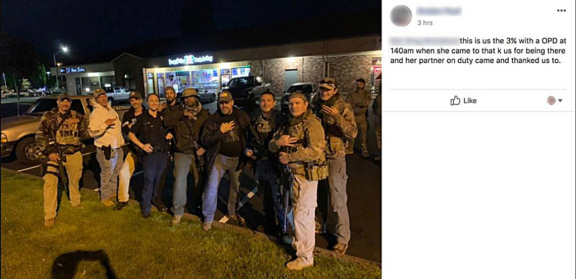 A group of men pose with guns and hold up three-