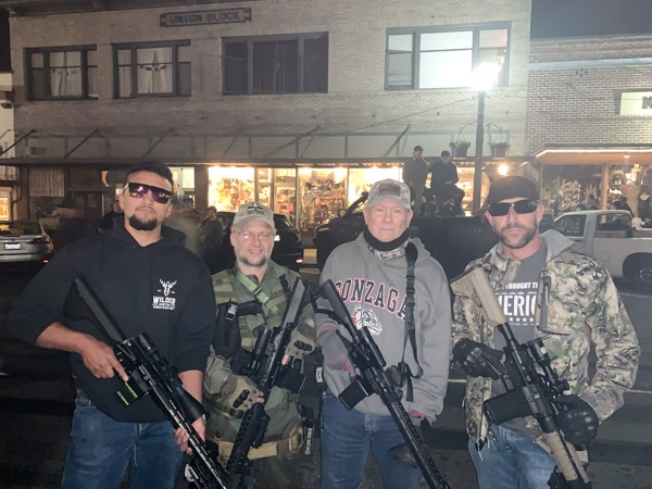 A group of four men post with guns.