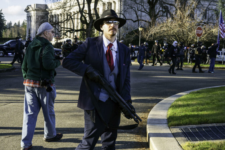A man dressed in a suit and hat holds a gun.