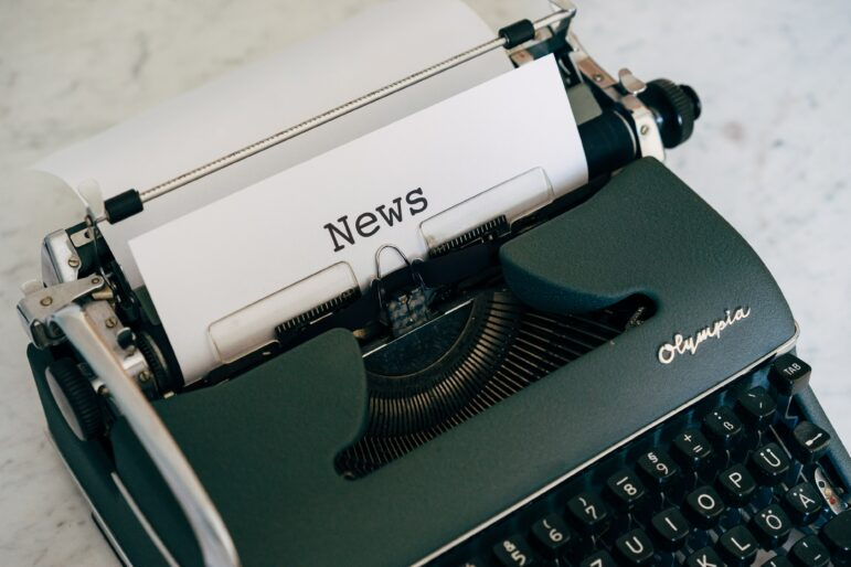 "typewriter holding a paper with the word ""news"" typed on it"