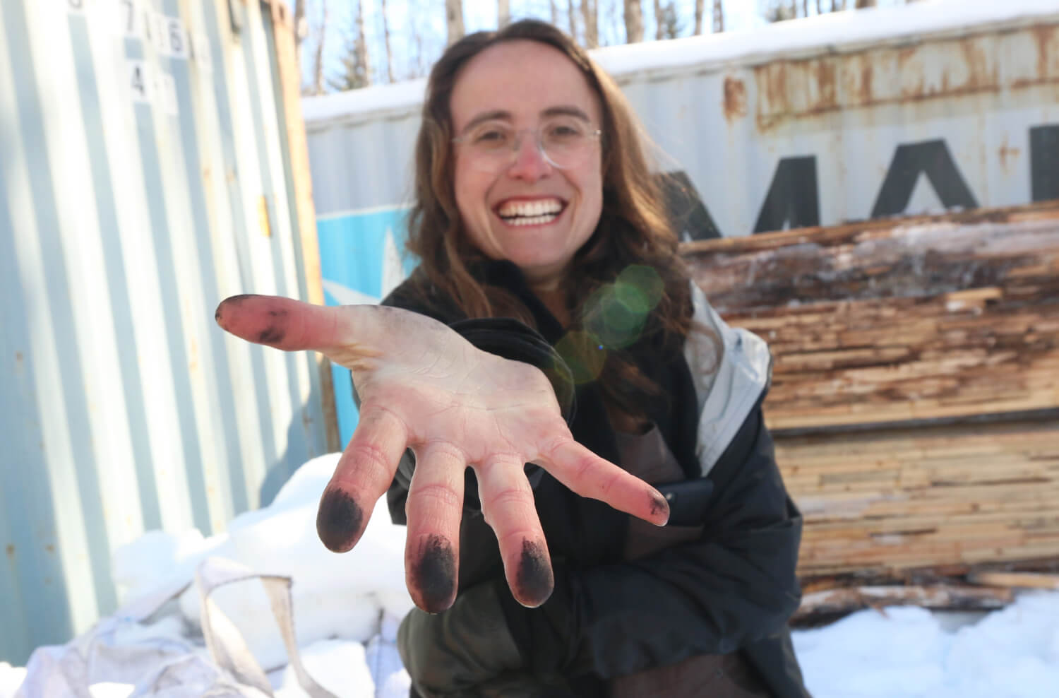 A person smiles at the camera and holds their hand outstretched toward the camera. There are black smudges on the fingerprints.