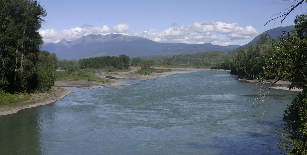 A landscape of water, with mountains in the background.