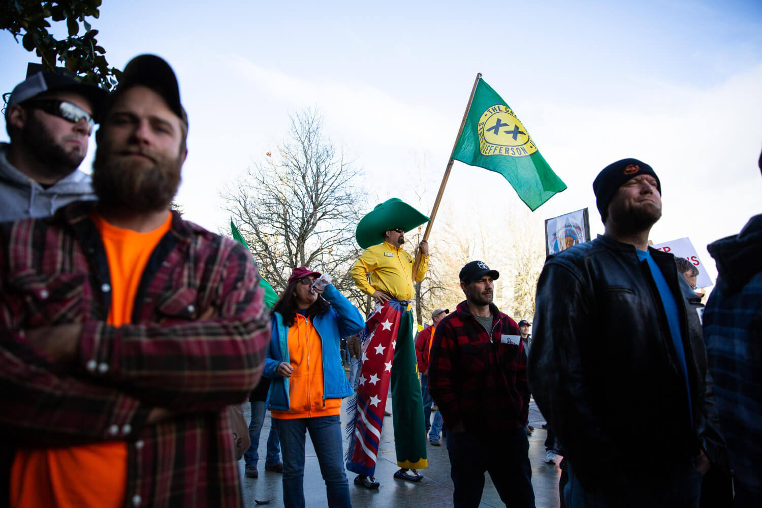 People stand in a loose crowd, and in the middle, there is a man in stilts dressed in yellow, red and green clothing with a large green hat, holding a flag.