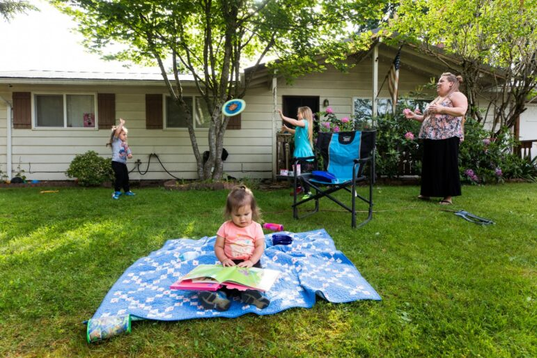 A child sits on a blanket outside, on grass, and reads a picture book while three family members play in the background.
