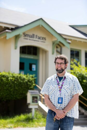 """A portrait of a person smiling and standing outside a building labeled """"Small Faces."""""""