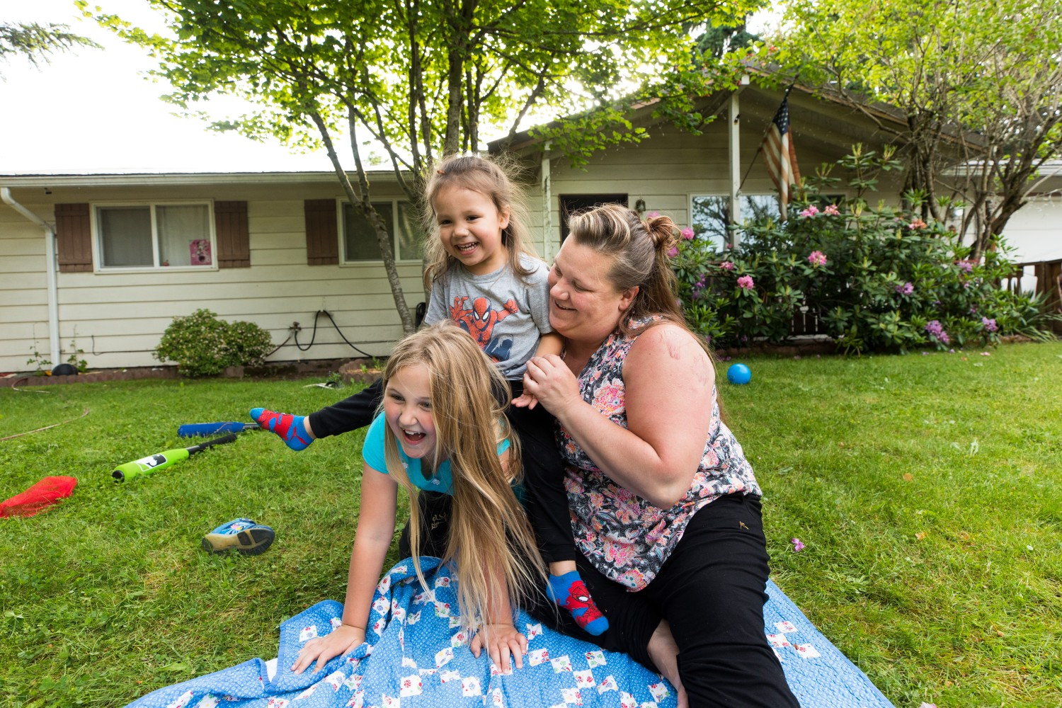 A mother playfully wrestles with her two children outside, on a residential lawn.