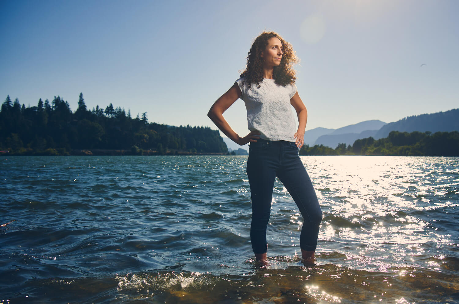 A person stands with their hands on their hips next to a river.