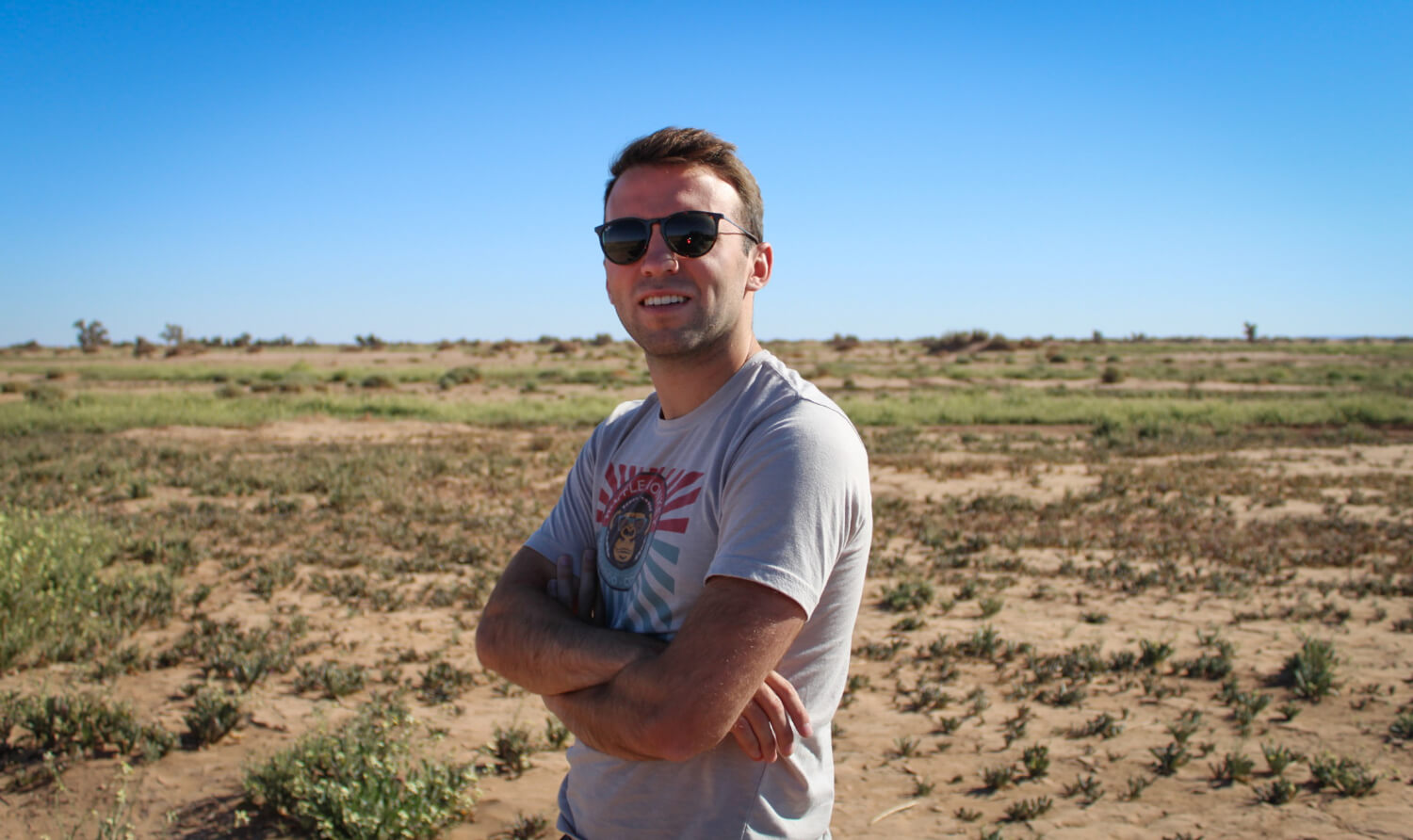 A person standing in a dry desert landscape with their arms crossed.