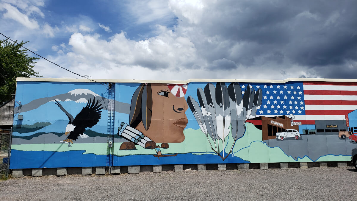 A mural depicting a bald eagle, the facial profile of a person from the Klamath Tribes, a U.S. flag, a parking lot, feathers, and a mountaintop.