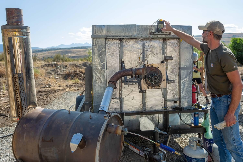 A person checks a gauge on a pyrolyzer.
