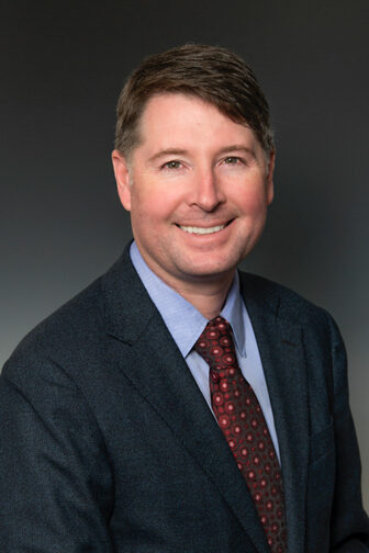 A professional headshot of a person in a business suit.
