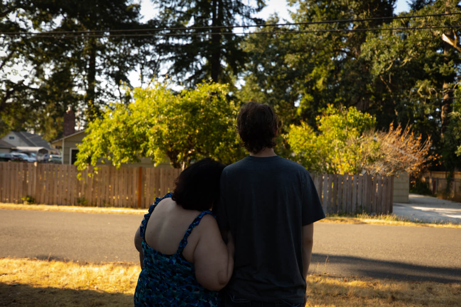 Two people embrace, facing away from the camera and looking out onto a residential street.