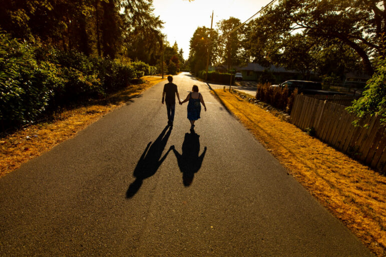 Two people walk on a road during sunset, holding hands.