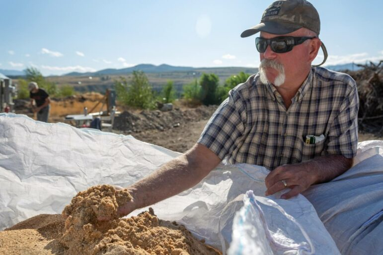 A person picks up a handful of sawmill dust and examines it.