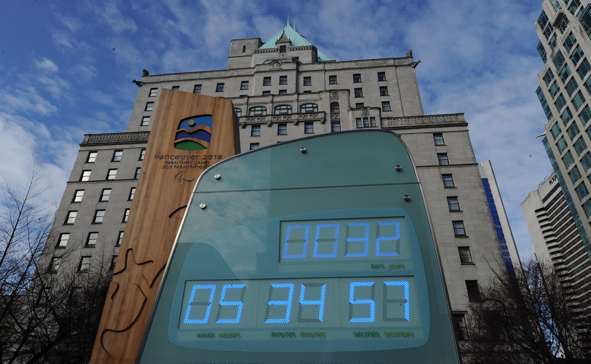 A giant digital clock in front of ab urban building.