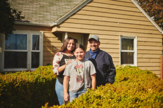 A family of three standing in front of a house, smiling.